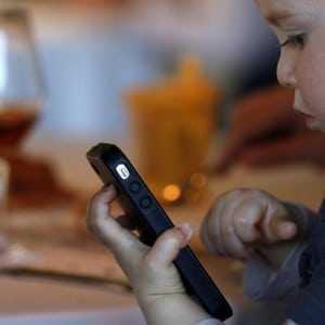 Un infant mirant-se un mòbil